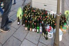 Μπουκάλια κρασιού και μπύρας που ανακυκλώνουν πλησίον το δοχείο στους ανθρώπους πόλεων Στοκ Εικόνες
