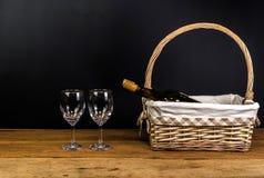 μπουκάλια κόκκινου κρασιού στο ψάθινο καλάθι στον ξύλινο πίνακα Στοκ Εικόνες