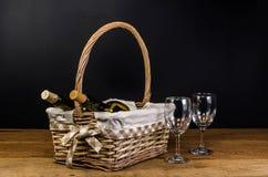 μπουκάλια κόκκινου κρασιού στο ψάθινο καλάθι στον ξύλινο πίνακα Στοκ εικόνες με δικαίωμα ελεύθερης χρήσης