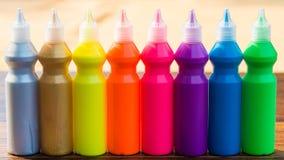 Μπουκάλια με τις ζωηρόχρωμες ξηρές χρωστικές ουσίες στο ξύλινο υπόβαθρο Στοκ φωτογραφία με δικαίωμα ελεύθερης χρήσης