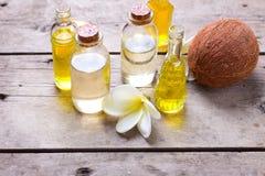 Μπουκάλια με το ουσιαστικό έλαιο αρώματος, την καρύδα και τα τροπικά λουλούδια Στοκ Εικόνες