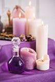 Μπουκάλια με το ουσιαστικό πετρέλαιο αρώματος και κεριά αρώματος το λουτρό εξαρτημάτων σημαδεύει τις πετσέτες SPA τιμής τών παραμ Στοκ Εικόνες