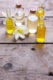 Μπουκάλια με το ουσιαστικό πετρέλαιο αρώματος και το τροπικό plumeria λουλουδιών Στοκ Εικόνα