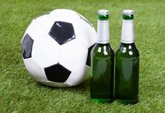 Μπουκάλια σφαιρών και μπύρας ποδοσφαίρου στην πράσινη χλόη Στοκ Εικόνες