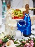Μπουκάλια της σαμπάνιας στα κοστούμια του νεόνυμφου και της νύφης στοκ φωτογραφία