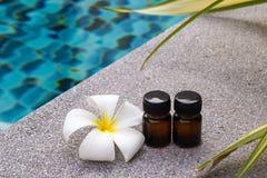 Μπουκάλια του ουσιαστικού πετρελαίου αρώματος και του λουλουδιού του frangipani ή plumeria στο υπόβαθρο πισινών Στοκ εικόνες με δικαίωμα ελεύθερης χρήσης