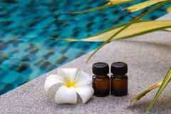 Μπουκάλια του ουσιαστικού πετρελαίου αρώματος και του λουλουδιού του frangipani ή plumeria στο υπόβαθρο πισινών Στοκ εικόνα με δικαίωμα ελεύθερης χρήσης