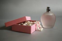 Μπουκάλι αρώματος και ρόδινο κιβώτιο με τις χάντρες μαργαριταριών σε ένα γκρίζο υπόβαθρο Στοκ Φωτογραφίες