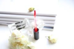 Μπουκάλι αρώματος, κόκκινο κραγιόν, άσπρα τριαντάφυλλα και περιοδικά Στοκ εικόνες με δικαίωμα ελεύθερης χρήσης
