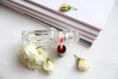 Μπουκάλι αρώματος, κόκκινο κραγιόν, άσπρα τριαντάφυλλα και περιοδικά Στοκ Εικόνα