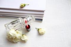 Μπουκάλι αρώματος, κόκκινο κραγιόν, άσπρα τριαντάφυλλα και περιοδικά Στοκ φωτογραφία με δικαίωμα ελεύθερης χρήσης