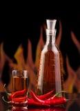 Μπουκάλι, βότκα γυαλιού, κόκκινο - καυτό πιπέρι τσίλι στις φλόγες υποβάθρου Στοκ Φωτογραφίες