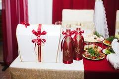 Μπουκάλι γαμήλιας σαμπάνιας σε ένα κόκκινο φόρεμα Στοκ Φωτογραφία