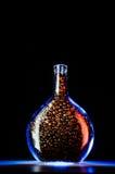 Μπουκάλι γυαλιού με τα φασόλια καφέ στο μπλε φως Στοκ φωτογραφίες με δικαίωμα ελεύθερης χρήσης