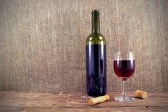 Μπουκάλι και ποτήρι του κρασιού στον πίνακα στοκ εικόνα