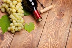 Μπουκάλι κόκκινου κρασιού και δέσμη των άσπρων σταφυλιών Στοκ Εικόνες