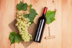 Μπουκάλι κόκκινου κρασιού και δέσμη των άσπρων σταφυλιών Στοκ φωτογραφία με δικαίωμα ελεύθερης χρήσης