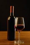 Μπουκάλι κόκκινου κρασιού με το γυαλί στο μαύρο υπόβαθρο Στοκ φωτογραφία με δικαίωμα ελεύθερης χρήσης