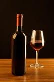 Μπουκάλι κόκκινου κρασιού με το γυαλί στο μαύρο υπόβαθρο Στοκ εικόνες με δικαίωμα ελεύθερης χρήσης