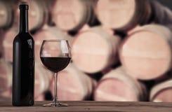 Μπουκάλι κόκκινου κρασιού με το γυαλί στο υπόβαθρο των δρύινων βαρελιών κόκκινο κρασί γυαλιού ανασκόπησης Στοκ Φωτογραφίες