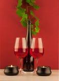 Μπουκάλι κόκκινου κρασιού με δύο wineglasses και κεριά Στοκ Εικόνα