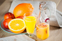 Μπουκάλι με έναν φρέσκο χυμό από τα πορτοκάλια και τα πορτοκάλια αίματος σε μια ξύλινη επιφάνεια Στοκ φωτογραφία με δικαίωμα ελεύθερης χρήσης