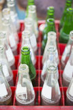 Μπουκάλι μη αλκοολούχων ποτών στα κόκκινα πλαστικά κλουβιά Στοκ εικόνα με δικαίωμα ελεύθερης χρήσης