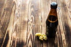 Μπουκάλι μπύρας με τους ξηρούς λυκίσκους Στοκ Φωτογραφίες