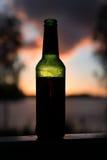 Μπουκάλι μπύρας που στέκεται μπροστά από τον ήλιο ρύθμισης στοκ φωτογραφίες με δικαίωμα ελεύθερης χρήσης