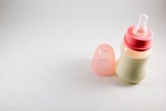 Μπουκάλι μωρών με το γάλα και ειρηνιστής σε ένα άσπρο υπόβαθρο Στοκ φωτογραφία με δικαίωμα ελεύθερης χρήσης