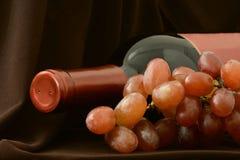 Μπουκάλι ξαπλώματος του κόκκινου κρασιού και δέσμη των σταφυλιών κοντά επάνω στοκ φωτογραφία