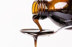 Μπουκάλι που χύνει ένα υγρό σε ένα κουτάλι η ανασκόπηση απομόνωσε το λευκό Φαρμακείο και υγιές υπόβαθρο Ιατρική Βήχας και κρύο φά στοκ εικόνα