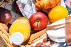 Μπουκάλι, ροδάκινα, Apple, πορτοκάλι και Croissant χυμού στο καλάθι πικ-νίκ Στοκ Εικόνες