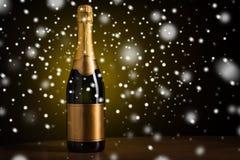 Μπουκάλι της σαμπάνιας με τη χρυσή ετικέτα πέρα από το χιόνι Στοκ Φωτογραφία