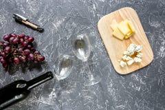 Μπουκάλι του κόκκινου κρασιού με το τυρί και του σταφυλιού aperitive στην γκρίζα τοπ άποψη επιτραπέζιου υποβάθρου πετρών Στοκ Εικόνες