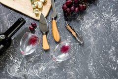 Μπουκάλι του κόκκινου κρασιού με το τυρί και του σταφυλιού aperitive στην γκρίζα τοπ άποψη επιτραπέζιου υποβάθρου πετρών copyspac Στοκ φωτογραφίες με δικαίωμα ελεύθερης χρήσης