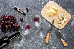 Μπουκάλι του κόκκινου κρασιού με το τυρί και του σταφυλιού aperitive στην γκρίζα τοπ άποψη επιτραπέζιου υποβάθρου πετρών Στοκ Φωτογραφίες