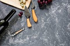 Μπουκάλι του κόκκινου κρασιού με το τυρί και του σταφυλιού aperitive στην γκρίζα τοπ άποψη επιτραπέζιου υποβάθρου πετρών copyspac Στοκ Εικόνα