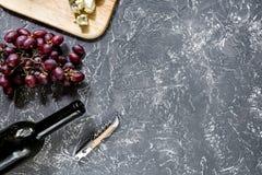 Μπουκάλι του κόκκινου κρασιού με το τυρί και του σταφυλιού aperitive στην γκρίζα τοπ άποψη επιτραπέζιου υποβάθρου πετρών copyspac Στοκ Φωτογραφίες