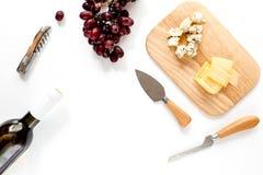 Μπουκάλι του κόκκινου κρασιού με το τυρί και του σταφυλιού aperitive στο άσπρο διάστημα υποβάθρου για τη τοπ άποψη κειμένων Στοκ Εικόνες