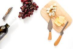 Μπουκάλι του κόκκινου κρασιού με το τυρί και του σταφυλιού aperitive στο άσπρο διάστημα υποβάθρου για τη τοπ άποψη κειμένων Στοκ Φωτογραφία