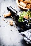 Μπουκάλι του κόκκινου κρασιού με το φρέσκο σταφύλι Στοκ Εικόνες