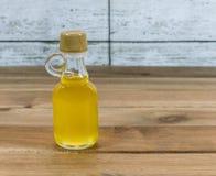 Μπουκάλι argan του πετρελαίου στον ξύλινο πίνακα Στοκ Εικόνες