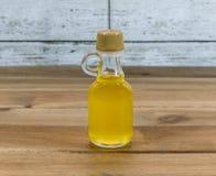 Μπουκάλι argan του πετρελαίου στον ξύλινο πίνακα Στοκ Εικόνα