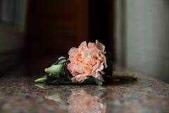 Μπουτονιέρα, λουλούδι τρυπών κουμπιών, μια κρέμα peonies στον πίνακα γρανίτη Στοκ Φωτογραφίες