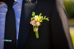 Μπουτονιέρα νεόνυμφων στο σακάκι του στοκ εικόνα