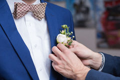 Μπουτονιέρα στον καθιερώνοντα τη μόδα νεόνυμφο στο γάμο στοκ φωτογραφία