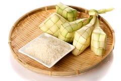 Μπουλέττα ρυζιού Ketupat και ρύζι στον παραδοσιακό υφαμένο δίσκο Στοκ Εικόνες