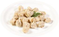 Μπουλέττες και μαϊντανός - ρωσικό pelmeni - ιταλικό ravioli - στο άσπρο πιάτο που απομονώνεται Στοκ Φωτογραφία