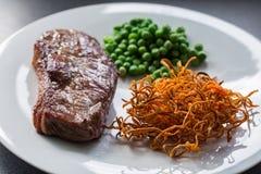 Μπριζόλα βόειου κρέατος με τα πράσινα μπιζέλια και τη γλυκιά πατάτα στοκ εικόνες